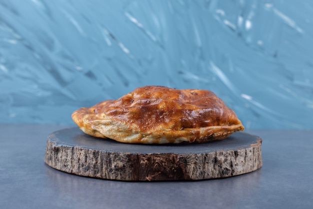 Tarte savoureuse sur une planche sur une table en marbre.