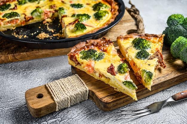 Tarte tranchée au saumon, brocoli et crème sur une planche à découper en bois