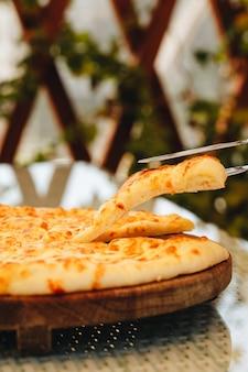 Tarte en tranches avec du fromage sur une planche de bois sur fond gris. khachapuri
