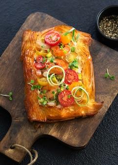 Tartelette apéritif faite maison de pâte feuilletée avec crevettes, gambas, tomates, avocat, légumes et micro-feuilles sur fond sombre.