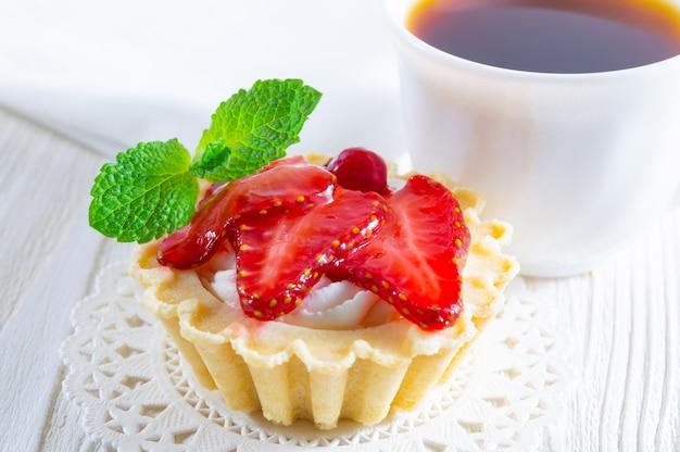 Tartelette aux fraises fraîches et au fromage à la crème, avec une tasse de thé et de petits biscuits.