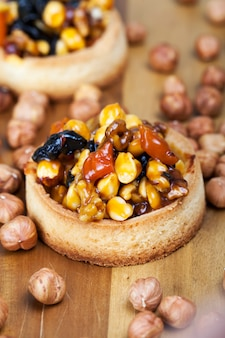 Tartelette de blé avec garniture sucrée, tartelette croustillante aux noisettes, cacahuètes et autres ingrédients, tartelette de pâte de blé aux noix et fruits secs en crème caramel