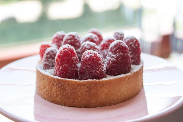 Tartelette à la framboise fraîche sur une assiette rose pastel enrobée de sucre en poudre.