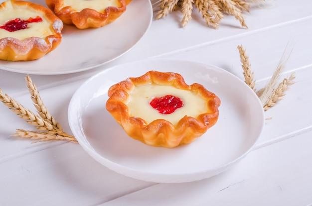 Tartelette savoureuse fraîche avec remplissage sur plaque blanche sur fond de bois blanc