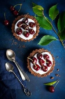 Tartelettes au chocolat avec de la crème et des baies fraîches de cerise douce sur une table en béton foncé. mise au point sélective vue de dessus.