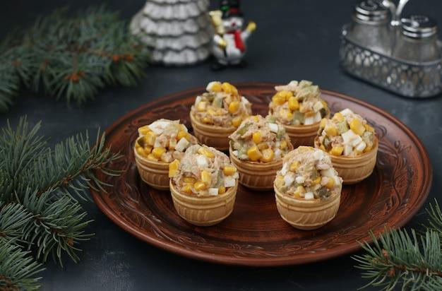 Tartelettes au thon, maïs et œufs sur une assiette sur fond sombre, format horizontal
