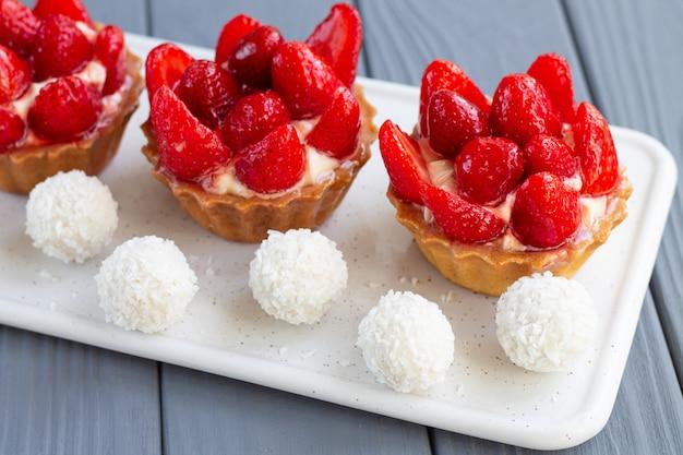 Tartelettes aux fraises fraîches et savoureuses ou gâteaux aux petits fruits et crème anglaise