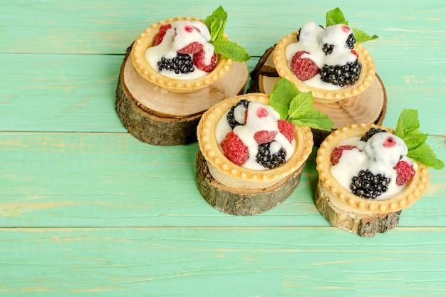 Tartelettes aux fruits rouges et crème, feuilles de menthe sur des souches décoratives.