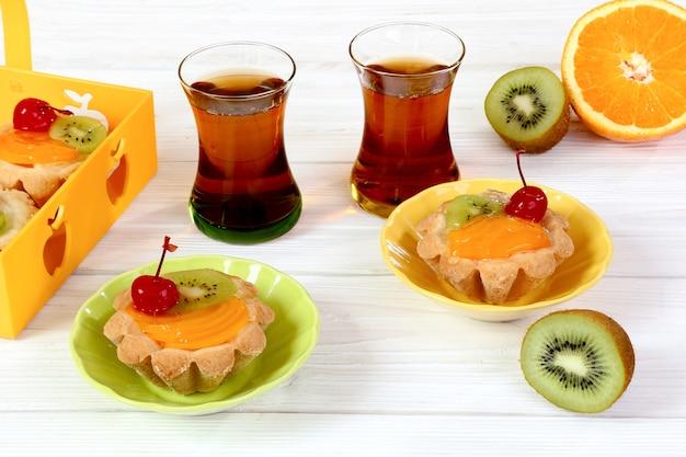 Tartelettes aux fruits et thé sur une table en bois blanc