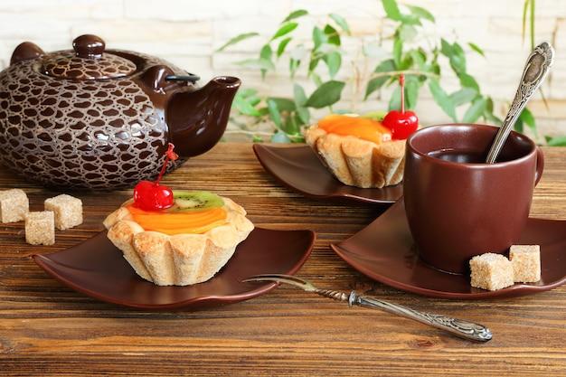Tartelettes aux fruits et thé sur une table en bois