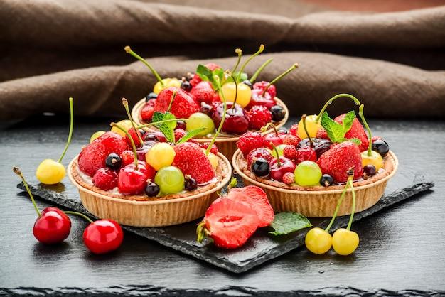 Tartelettes aux petits fruits avec myrtilles, framboises, kiwi, fraises, flocons d'amandes au sucre glace.