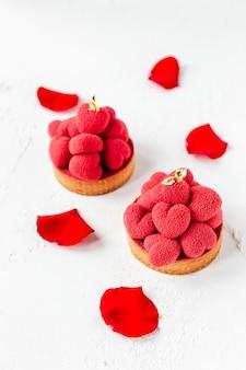 Tartelettes de dessert sucré avec des coeurs de mousse rouge sur le dessus, décorées de pétales de roses rouges