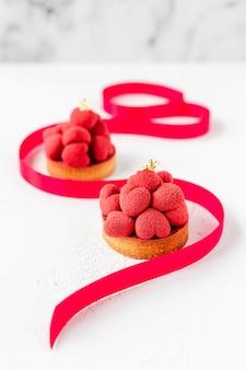 Tartelettes de dessert sucré avec des coeurs de mousse rouge sur le dessus, décorées d'un ruban