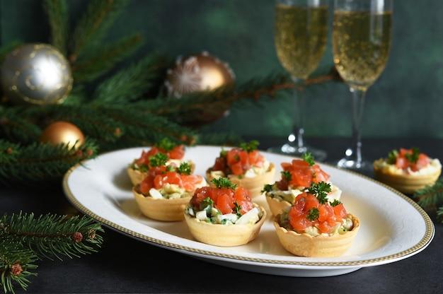 Tartelettes farcies de salade et saumon sur une table du nouvel an