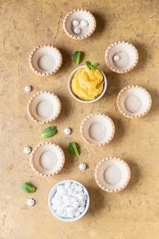Tartelettes sablées vides, caillé de citron, mini meringues et menthe sur une surface en béton