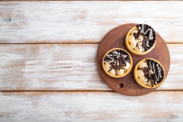 Tartelettes sucrées au chocolat et crème au fromage sur un fond en bois blanc. vue de dessus, mise à plat, espace de copie.