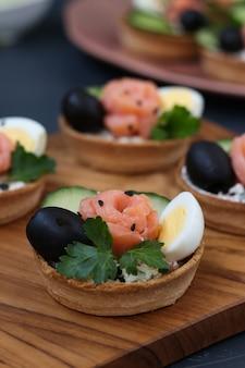 Tartelettes de vacances avec fromage, saumon, olives noires, œufs de caille et concombres sur planche de bois sur une surface sombre, orientation verticale, gros plan