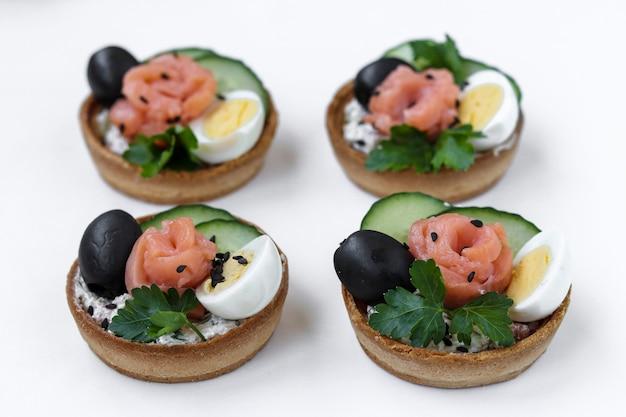Tartelettes de vacances avec fromage, saumon, olives noires, œufs de caille et concombres sur surface blanche
