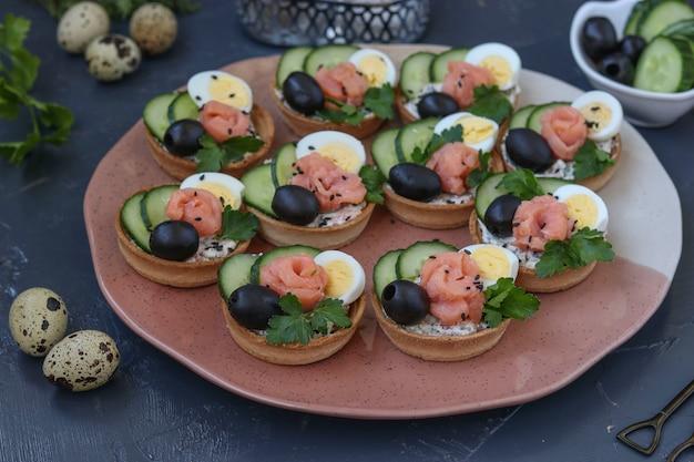 Tartelettes de vacances avec fromage, saumon, olives noires, œufs de caille et concombres sur une surface sombre, orientation horizontale, gros plan