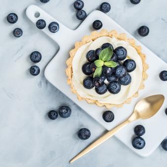 Tartelettes à la vanille avec des baies de bleuets et des couverts en or sur fond clair.