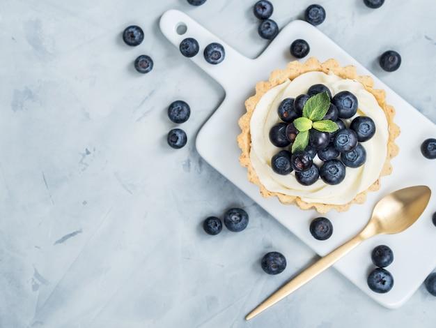 Tartelettes à la vanille avec des baies de myrtille sur fond clair.