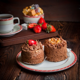 Tartes au chocolat avec fraise et sucre et tasse de thé en assiette