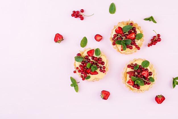Tartes aux fraises, cassis et crème fouettée à décor de feuilles de menthe, vue de dessus
