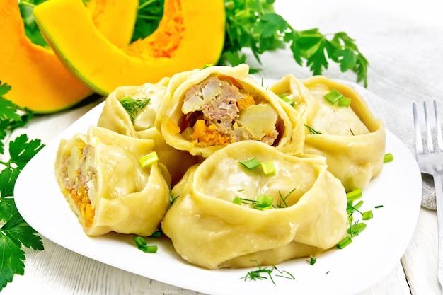 Tartes cuites à la vapeur manty avec de la viande hachée et de la citrouille, des oignons verts dans une assiette, une serviette, du persil et une fourchette sur fond de planche de bois
