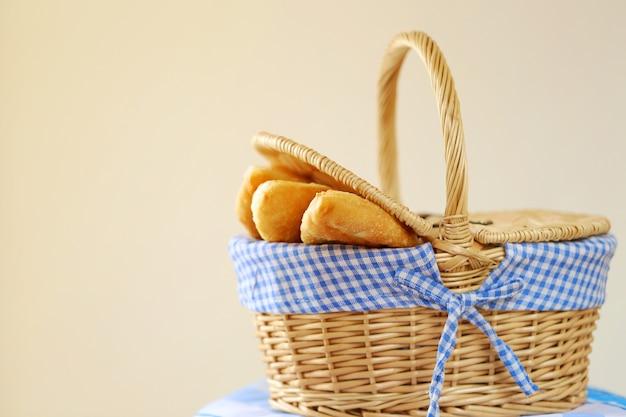 Tartes frites dans un panier en osier sur une serviette de table rayée bleue sur beige