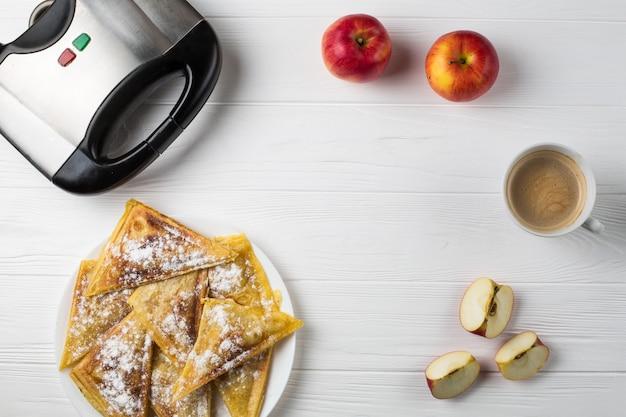 Des tartes sont posées sur la table à côté de pommes, d'un grille-pain et d'une tasse de café