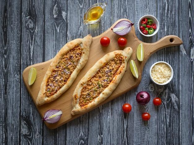 Tartes à la viande libanaises traditionnelles sur une table en bois noire