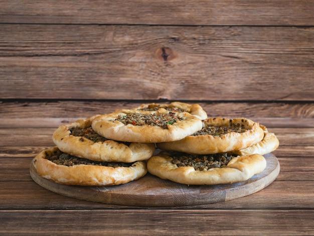 Tartes à la viande libanaises traditionnelles sur une table en bois