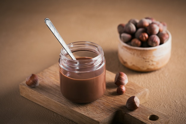 Tartinade de lait aux noisettes au chocolat fait maison sur une surface brune