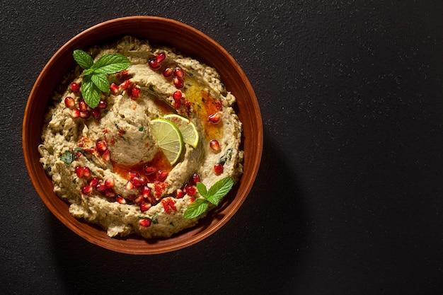 Tartinade maison de baba ganoush aubergine cuit au four dans un bol avec des graines de grenade, de la chaux, de l'huile d'olive et des tranches de citron vert sur fond noir