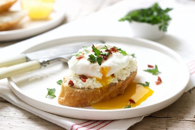 Tartines croustillantes à la baguette avec fromage cottage, œuf poché et tomates séchées sur fond clair.