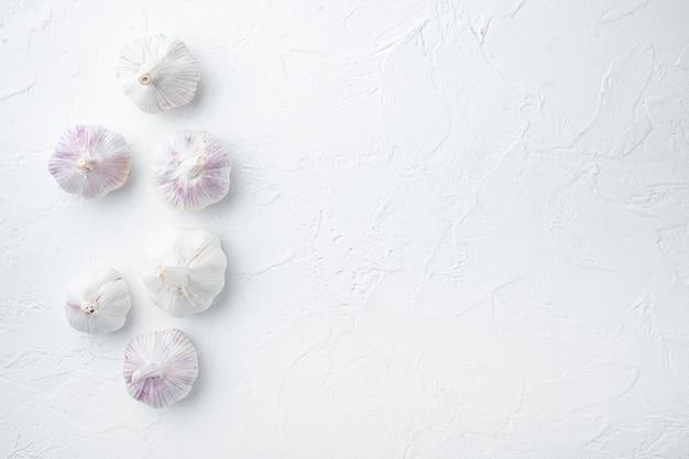 Tas d'ail de ferme biologique, sur fond blanc, vue de dessus à plat, avec fond et espace pour le texte