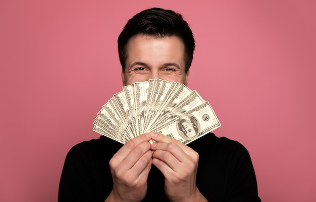 Un tas d'argent. jeune homme heureux, qui regarde dans la caméra tout en couvrant son visage avec une pile de billets.