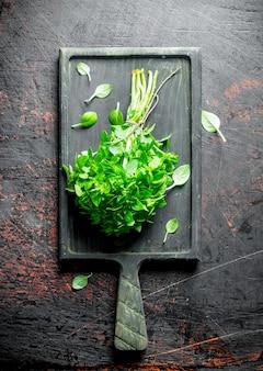 Tas de basilic frais sur la planche à découper sur table rustique
