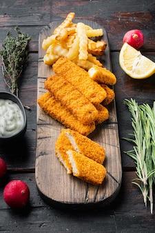 Tas de bâtonnets de poisson frits dorés avec sauce à l'ail blanc, sur une planche à découper en bois, sur un vieux fond de table en bois foncé