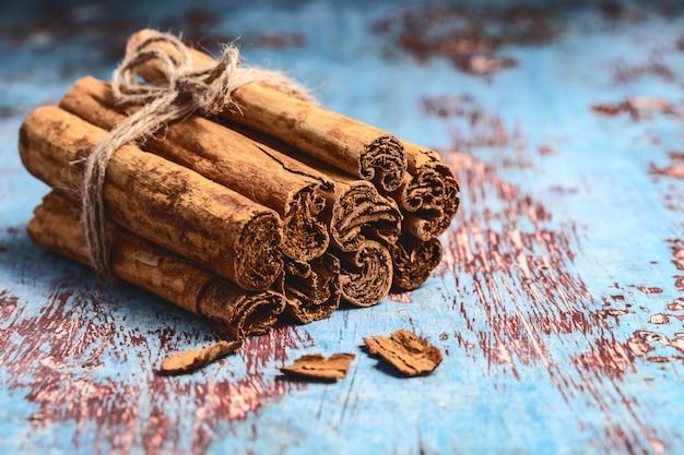 Tas de bâtons de cannelle indienne fraîche sur une table en bois bleue