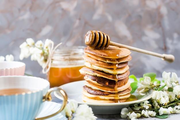 Un tas de beignets à côté d'une tasse de thé et un pot de miel sur un fond gris