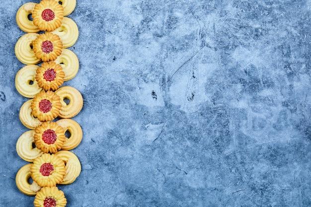 Tas de biscuits assortis sur fond bleu.