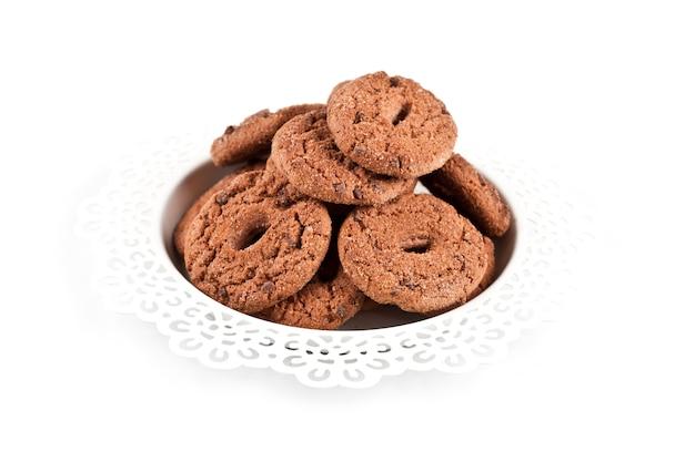 Tas de biscuits aux pépites de chocolat fraîches au four sur une plaque blanche isolée