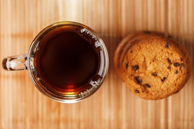 Un tas de biscuits à l'avoine avec des pépites de chocolat et une tasse de thé noir chaud parfumé
