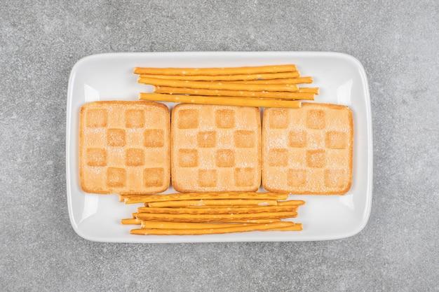 Tas de biscuits et bretzels sur plaque blanche