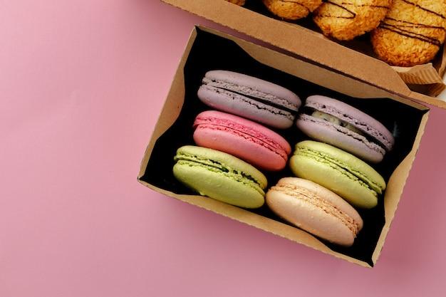 Tas de biscuits macarons colorés sur fond rose