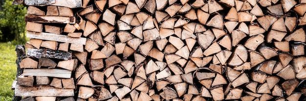 Un tas de bois avec la récolte et le bois de chauffage empilé de bois coupé pour allumer et chauffer la maison. bois de chauffage du bouleau. bannière