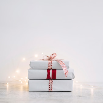 Tas de boîtes-cadeaux blanches avec guirlande sur table