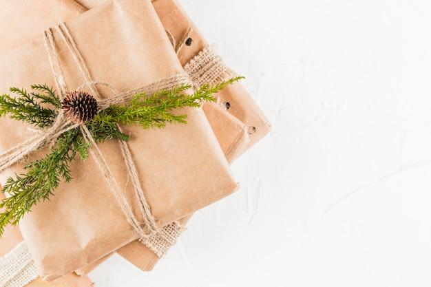 Tas de boîtes présentes en papier kraft avec une branche de conifère