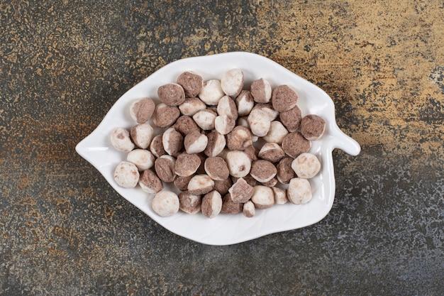 Tas de bonbons bruns sur plaque en forme de feuille.